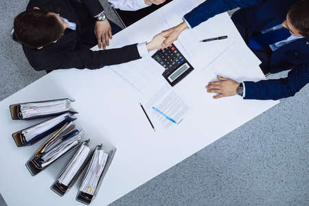 Photo pour Business people shaking hands at meeting, view from above. Bookkeeper or financial inspector making report, calculating or checking balance. Internal Revenue Service checking financial document. Audit and tax concept - image libre de droit