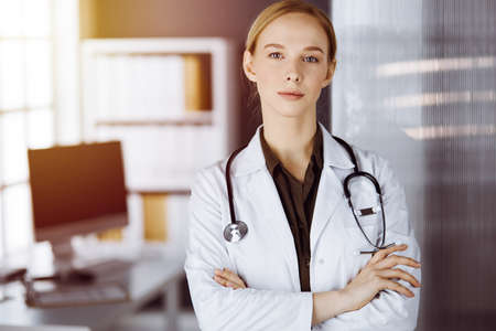 Photo pour Cheerful smiling female doctor standing with arms crossed in clinic. Portrait of friendly physician woman. Medicine concept - image libre de droit