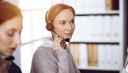 Photo pour Businesswoman talking by headset in sunny office. Call center and diverse people group in business - image libre de droit