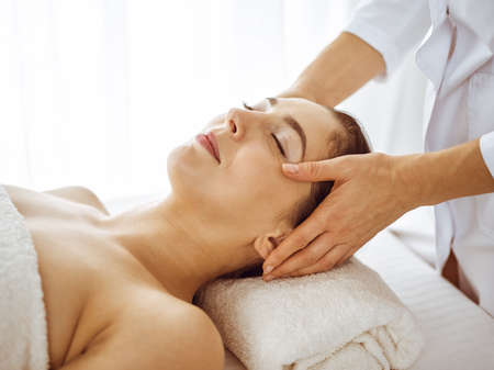 Photo pour Beautiful brunette woman enjoying facial massage with closed eyes. Relaxing treatment in medicine and spa center concepts. - image libre de droit
