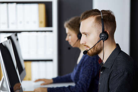 Photo for Red-bearded businessman talking by headset near his female colleague while sitting in modern office. Diverse people group in call center. Telemarketing and customer service - Royalty Free Image