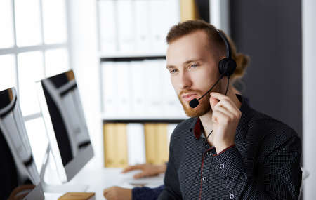 Photo pour Red-bearded businessman talking by headset near his female colleague while sitting in modern office. Diverse people group in call center. Telemarketing and customer service - image libre de droit