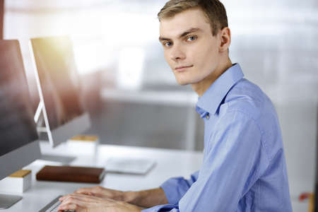 Foto de Young successful businessman works with computer, sitting at the desk in a sunny modern office. Headshot of male entrepreneur or it-specialist at workplace. Business concept - Imagen libre de derechos