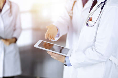 Group of unknown doctors use a computer tablet to check up some medical names records, while standing in a sunny hospital office. Physicians ready to examine and help patients. Medical help, insurance in health care, best desease treatment and medicine co