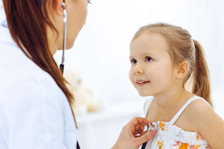 Photo pour Doctor examining a little girl by stethoscope. Happy smiling child patient at usual medical inspection. Medicine and healthcare concepts - image libre de droit