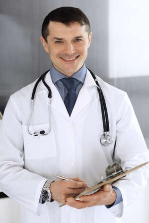 Photo pour Doctor man using clipboard for filling up medication history records. Perfect medical service in clinic. Physician at work in hospital. Medicine and healthcare concepts - image libre de droit