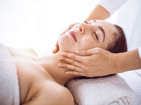 Photo pour Beautiful brunette woman enjoying facial massage with closed eyes in sunny spa center . Relaxing treatment and cosmetic medicine concepts - image libre de droit