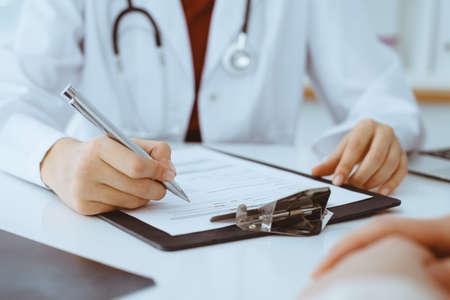 Photo pour Unknown woman-doctor filling up an application form while consulting patient. Medicine concept - image libre de droit