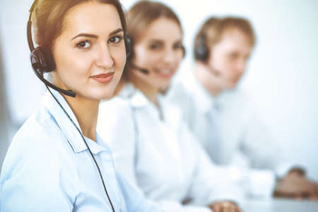 Photo pour Call center. Focus on beautiful business woman in headset - image libre de droit