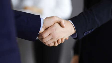 Photo pour Business people shaking hands at meeting or negotiation, close-up. Group of unknown businessmen and a woman stand together in a modern office. Teamwork, partnership and handshake concept - image libre de droit