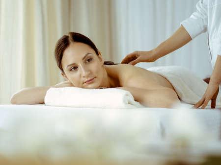 Photo pour Pretty brunette woman enjoying treatment with hot stones in spa salon. Beauty concept - image libre de droit