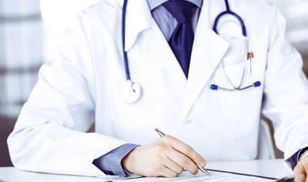 Photo for Unknown male doctor sitting and working with clipboard in clinic at his working place, close-up. Young physician at work. Perfect medical service, medicine concept - Royalty Free Image