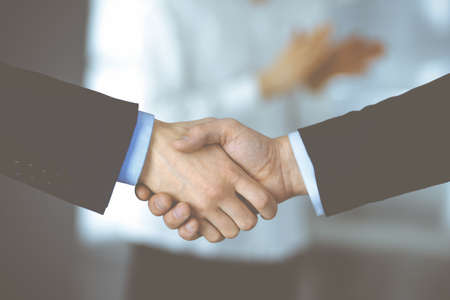 Photo pour Business people shaking hands at meeting or negotiation, close-up. Group of unknown businessmen and a woman standing in a modern office. Teamwork, partnership and handshake concept - image libre de droit