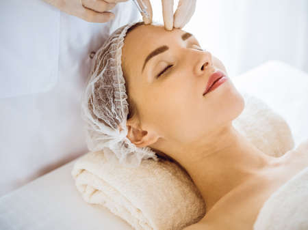 Photo pour Beautiful woman receiving beauty injections with closed eyes in medical center. Beautician doctor hands doing beauty procedure to female face with syringe. Cosmetic medicine and surgery concept - image libre de droit