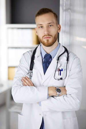 Photo pour Red-bearded doctor standing straight in clinic near his working place. Portrait of physician. Medicine, healthcare - image libre de droit