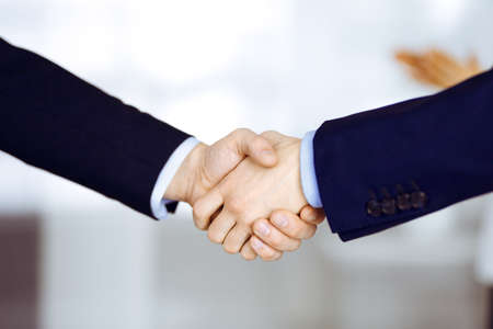 Photo pour Business people shaking hands, close-up. Group of unknown businessmen standing in a modern office. Teamwork, partnership and handshake concept - image libre de droit