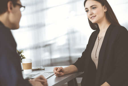Photo pour Young friendly business people are talking to each other, while sitting at the desk in a modern office. Focus on woman. Concept of business success - image libre de droit