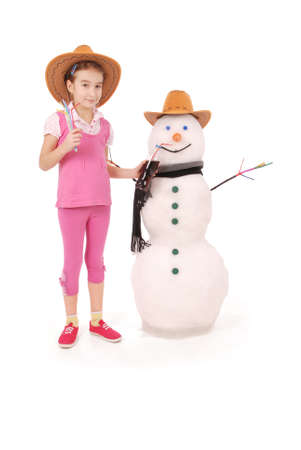 Cute girl holding a cola bottle near a snowman with scarf and hat on white background