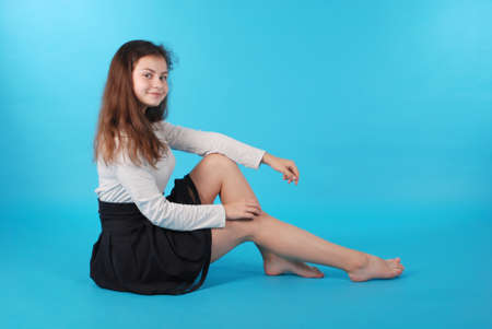 Photo pour Young girl sitting on floor against blue background in studio. - image libre de droit