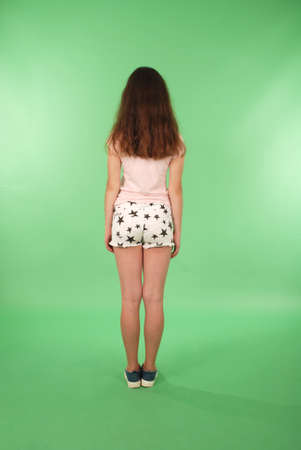 Foto de Rear view young girl with long hair looking at wall. Isolated on green background - Imagen libre de derechos