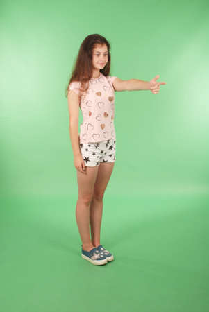 Foto de Side view young girl with raised hand looking at wall. Isolated on green background - Imagen libre de derechos