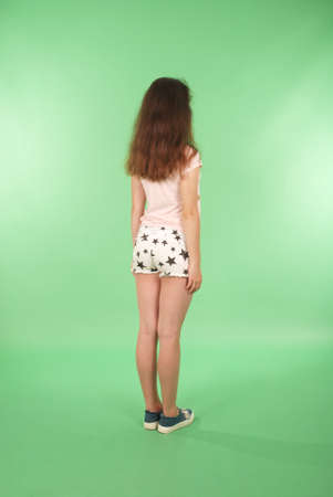Foto de Side view young girl with long hair looking at wall. Isolated on green background - Imagen libre de derechos