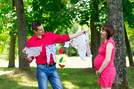young couple man and his pregnant wife in summer park