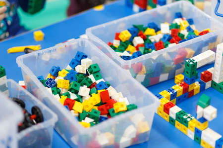 Foto de Close up of child's hands playing with colorful plastic bricks at the table. The first steps for the development of engineering type of thinking. - Imagen libre de derechos