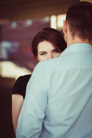 Photo for Portrait of young woman looking from behind the shoulder of her boyfriend. Love concept. - Royalty Free Image