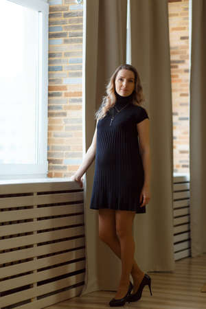Photo pour Thoughtful pregnant woman caressing her belly and looking in camera. Full length. - image libre de droit