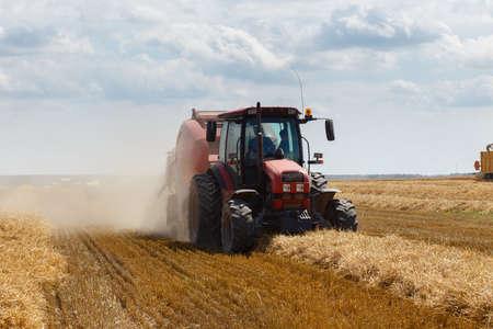Photo pour A round baler discharges a fresh wheat bale during harvesting. - image libre de droit