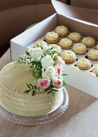 Foto de wedding cake with fresh flowers and cupcakes on a light background - Imagen libre de derechos