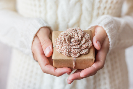 Woman in white knitted sweater holding a present. Gift is packed in craft paper with hand made crocheted flower. Example of DIY ways to pack Cristmas and other presents.