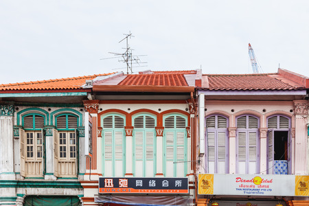 SINGAPORE, SINGAPORE - January 16, 2013. Colonial architecture of city. Buildings with many decorative elements, colorful jalousie and shop signs.