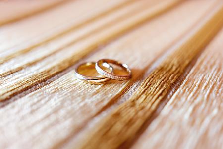 Foto de Golden wedding rings with diamonds on beige fabric background. Wedding details, symbol of love and marriage. - Imagen libre de derechos