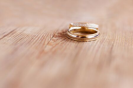 Foto de Pair of golden wedding rings with diamonds on shabby wooden background. Symbol of love, marriage and the fifth (wooden) wedding anniversary. - Imagen libre de derechos