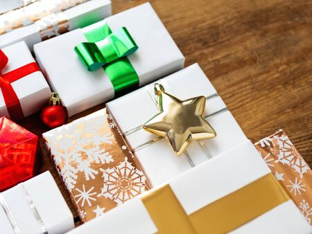 Photo for Christmas presents on shabby wooden background. Gifts in white and golden paper with bright golden riboons on with sparkling star confetti. - Royalty Free Image