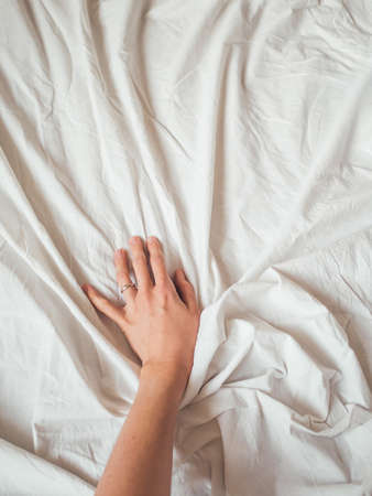 Photo pour Woman's hand on background of crumpled bed sheet. Creased white linen. Woman touches unmade bed. Cozy imperfect house. Non-ideal cozy home. - image libre de droit