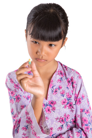 A young Asian Malay girl with face expressions and medicinal tablets over white background