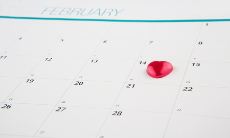 Red heart shape symbol on the February 14th date on a calendar for Valentine\\\\