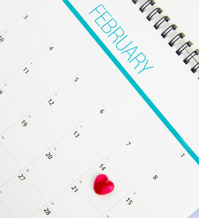 Red heart shape symbol on the February 14th date on a calendar for Valentine\'s Day