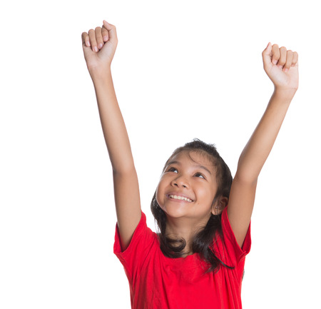 Young Asian girl raising her hands over white background