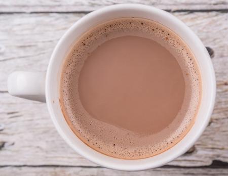 Photo pour A mug of hot chocolate over wooden background - image libre de droit