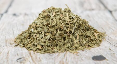 Dried tarragon herb over wooden background