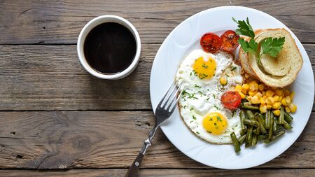 Photo for Fried eggs with tomatoes, green beans, corn and toast. English vegetarian breakfast. Top view. Coffee and fried eggs on a wooden tray. Wood background - Royalty Free Image
