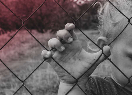 Photo for The child holds an iron fence with his hand. Sad child. Cruelty to children. - Royalty Free Image