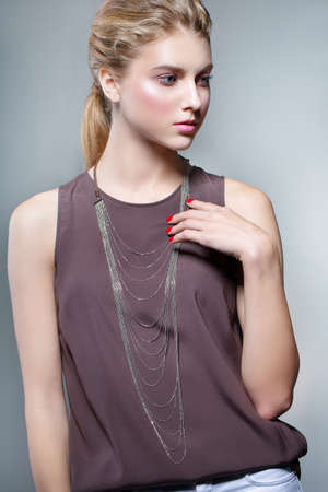 Photo pour Beauty fashion portrait of a young beautiful girl posing in the Studio. Bright evening makeup, stylish clothes. Hand touches decoration - image libre de droit