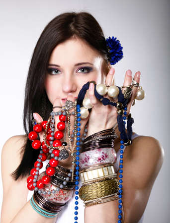 young woman in summer style with plenty of jewellery, beads in hands gray background