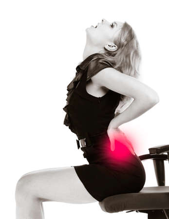 Young businesswoman with backache. Blond woman with back pain sitting on chair. Long working hours. Bussiness. Black white photo. Isolated. Studio shot.