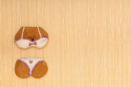 Funny bikini shape gingerbread cake cookie sweet dessert with white icing and violet purple decoration border or frame on beige bamboo mat